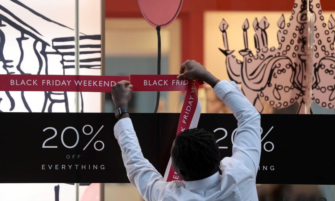 Funcionário cola anúncios de descontos na vitrine de uma loja em Oxford Street, Londres Foto: SIMON DAWSON / REUTERS