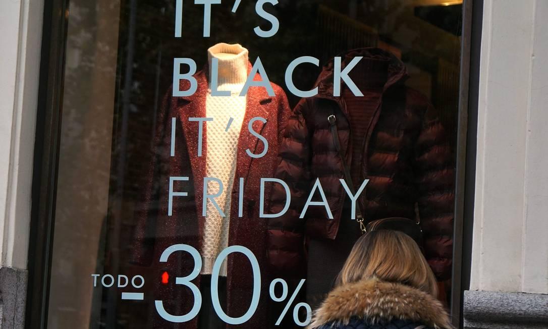 """Consumidora observa anúncio de descontos para a """"Black Friday"""", em Madri Foto: GABRIEL BOUYS / AFP"""