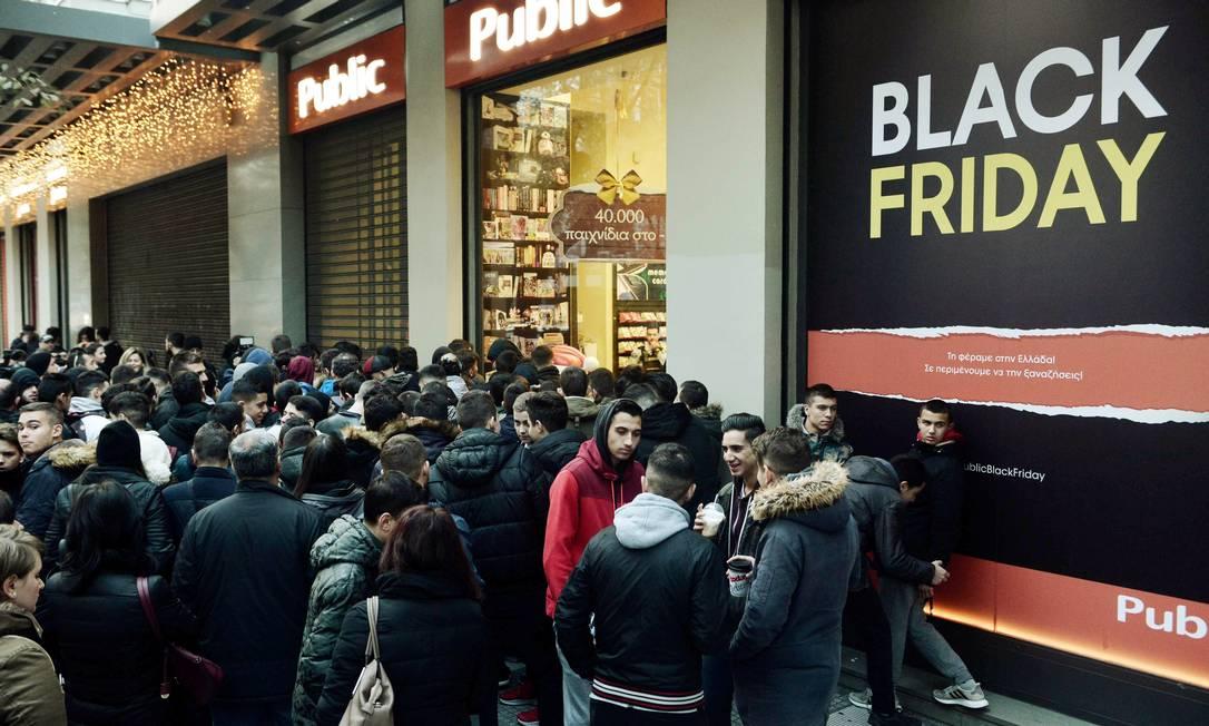 As pessoas aguardam em filas fora de uma loja de departamento em Tessalônica, na Grécia, para poder aproveitarem as ofertas da Black Friday Foto: SAKIS MITROLIDIS / AFP