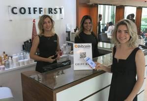 A empresária Luciana Taihs explica aos clientes como se faz o pagamento em bitcoin pelo celular Foto: Rodrigo Berthone / Agência O Globo