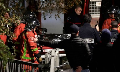 Policiais transportam o corpo do animal morto em Paris Foto: THOMAS SAMSON / AFP