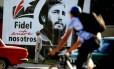 Cubanos passam por pôster com a imagem de Fidel Castro em Havana: país lembra um ano da morte de seu líder revolucionário neste sábado Foto: AFP/YAMIL LAGE