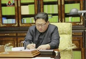 O líder norte-coreano assina o que seria um documento que autoriza do teste com míssil balístico Foto: AP