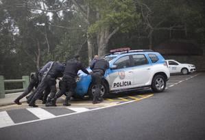 Policiais empurram o carro em pane durante patrulhamento na Vista Chinesa Foto: Márcia Foletto / Agência O Globo