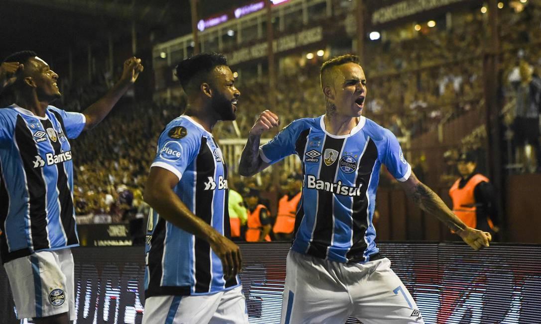 Luan, à direita, comemora o segundo gol ao lado de Fernandinho, que marcou o primeiro Foto: EITAN ABRAMOVICH / AFP