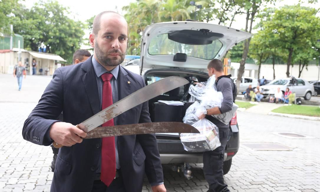 O delegado André Leiras com os dois facões apreendidos na sala de um dirigente do Botafogo no Estádio Nilton Santos Foto: Fabiano Rocha / Fabiano Rocha