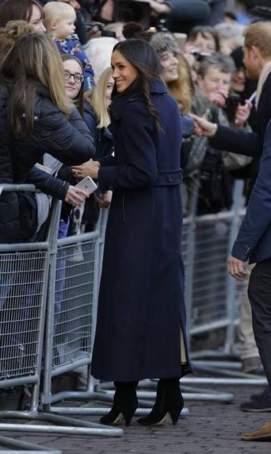 Meghan manteve o casaco abotoado enquanto saudava a multidão que acompanhou a chegada do casal à cidade de Nottingham, no Reino Unido Alastair Grant / AP