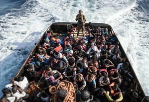 Soldado líbio escolta grupo de imigrantes ilegais que tentavam entrar na Europa Foto: TAHA JAWASHI / AFP