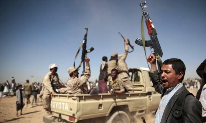 Homens leais a rebeldes xiitas houthi entoam gritos de guerra em confronto com forças pró-governo em Sanaa- Hani Mohammed  AP