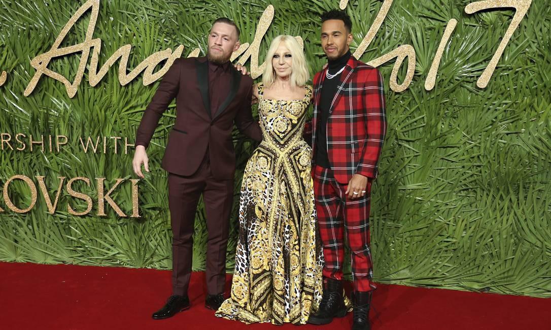 A estilista Donatella Versace entre o lutador Conor McGregor (esquerda) e o piloto de Fórmula 1 Lewis Hamilton Joel C Ryan / Joel C Ryan/AP