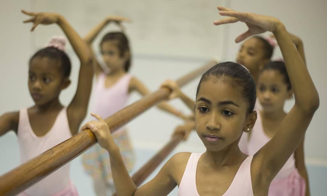 As pequenas bailarinas do Vidançar, no Complexo do Alemão, mostram concentração nos movimentos durante a aula Julio Cesar Guimaraes / Agência O Globo