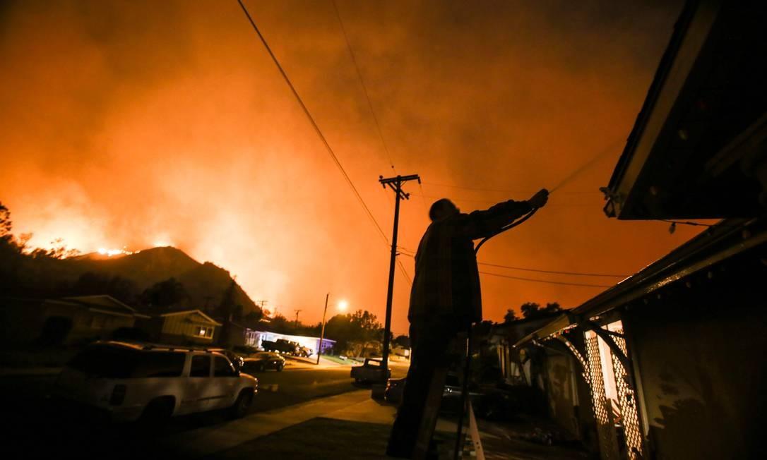 Morador molha sua casa com mangueira na tentativa de conter as chamas em Santa Paula, condado de Ventura, Califórnia RINGO CHIU / AFP