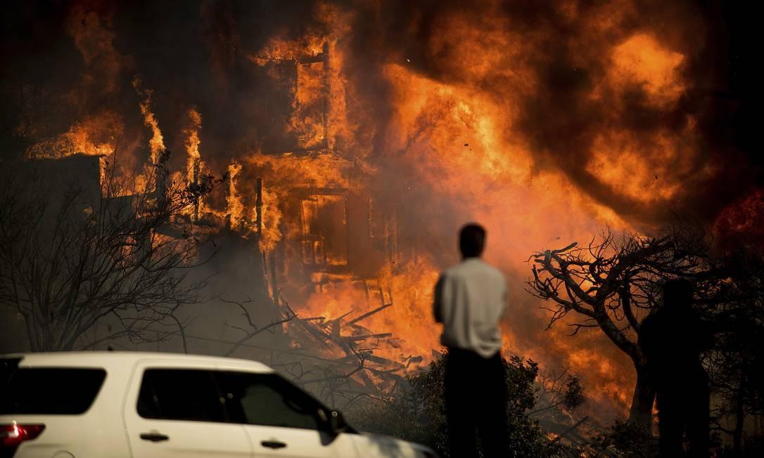 Homem observa as chamas consumirem uma residência durante o mais violento incêncio das últimas décadas Noah Berger / AP
