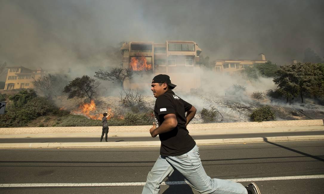 Emanuel Vasquez, de Oxnard, Califórnia, passa por uma residência em chamas na Foothill Road. O incêndio obrigou milhares de pessoas a deixarem suas casas Noah Berger / AP