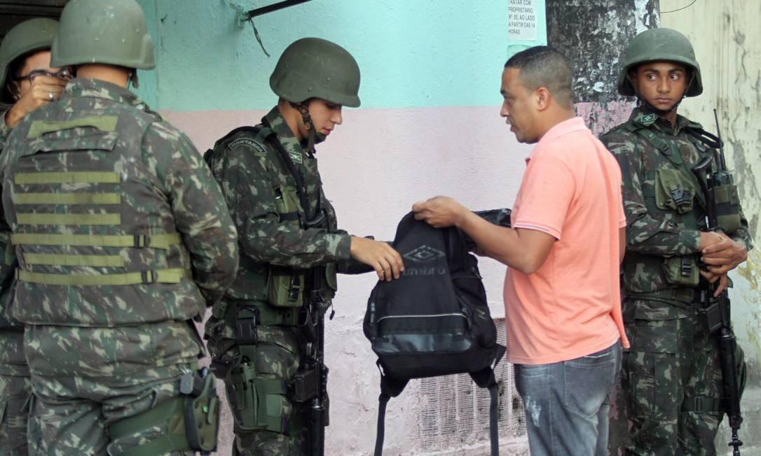 Militares vistoriam mochila de morador durante a operação Foto: Paulo Nicolella / Agência O Globo