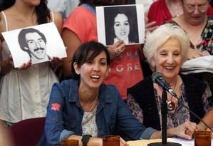 Adriana, à direita, ao lado da presidente das Avós da Praça de Maio, Estela de Carlotto; ao fundo fotos dos pais de Adriana Foto: BERNARDINO AVILA / REUTERS