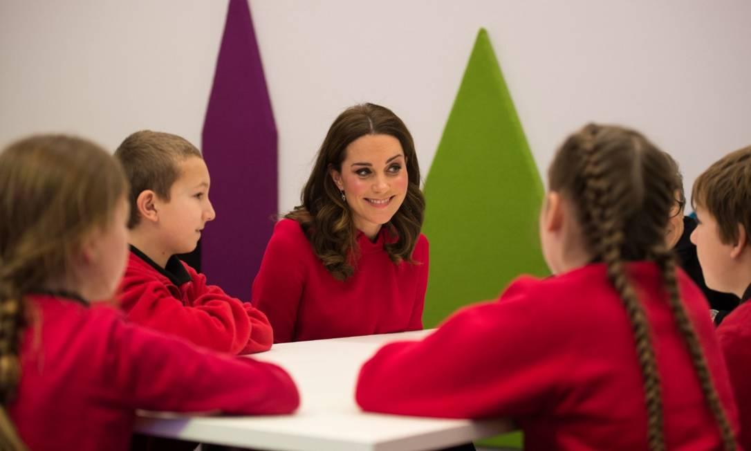 """As crianças selecionadas para visitar o centro de mídia da BBC durante a cúpula mundial de mídia infantil, na Inglaterra, nesta quarta-feira, não se mostraram muito impressioandas com a visita do princípe William e de Kate Middleton ao evento, de acordo com o jornal britânico """"Daily Mail"""". O look da duquesa de Cambridge pode ter contribuído para a baixa comoção: usando vestido da exata cor do uniforme das crianças, ela se integrava perfeitamente e, por vezes, sumia na multidão de casacos vermelhos OLI SCARFF / AFP"""