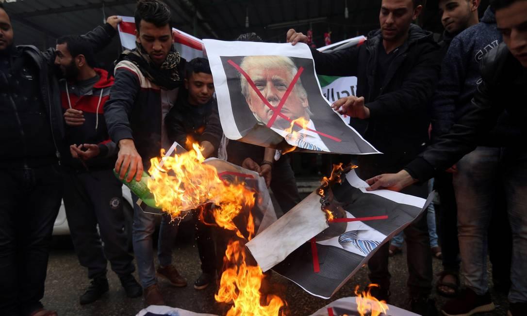 Palestinos na Faixa de Gaza queimam fotos do presidente americano, Donald Trump, e do primeiro-ministro israelense, Benjamin Netanyahu, durante um protesto contra a intenção dos EUA de transferirem sua representação diplomática de Tel Aviv para Jerusalém IBRAHEEM ABU MUSTAFA / REUTERS