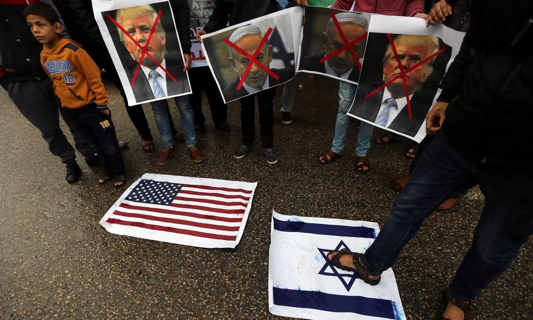 Palestino pisa num pôster da bandeira de Israel enquanto outros manifestantes seguram fotos de Trump e Netanyahu durante um protesto na Faixa de Gaza. O presidente americano foi alvo de forte pressão para que não reconhecesse Jerusalém como capital de Israel, já que a decisão pode causar instabilidade nas negociações de paz entre Israel e palestinos IBRAHEEM ABU MUSTAFA / REUTERS