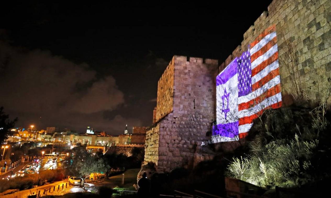 Bandeiras gigantes de Israel e EUA são projetadas nas muralhas da Cidade Velha de Jerusalém. O presidente americano, Donald Trump, contrariou as pressões internacionais e anunciou na tarde desta quarta-feira que reconhece a cidade como capital de Israel Foto: AHMAD GHARABLI / AFP