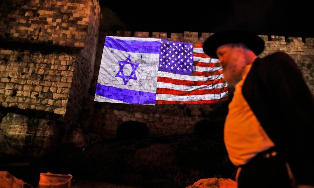 Homem passa em frente às bandeiras americana e israelense nos muros da Cidade Velha de Jerusalém. Decisão de Trump de reconhecer cidade como capital de Israel diverge do consenso internacional AHMAD GHARABLI / AFP