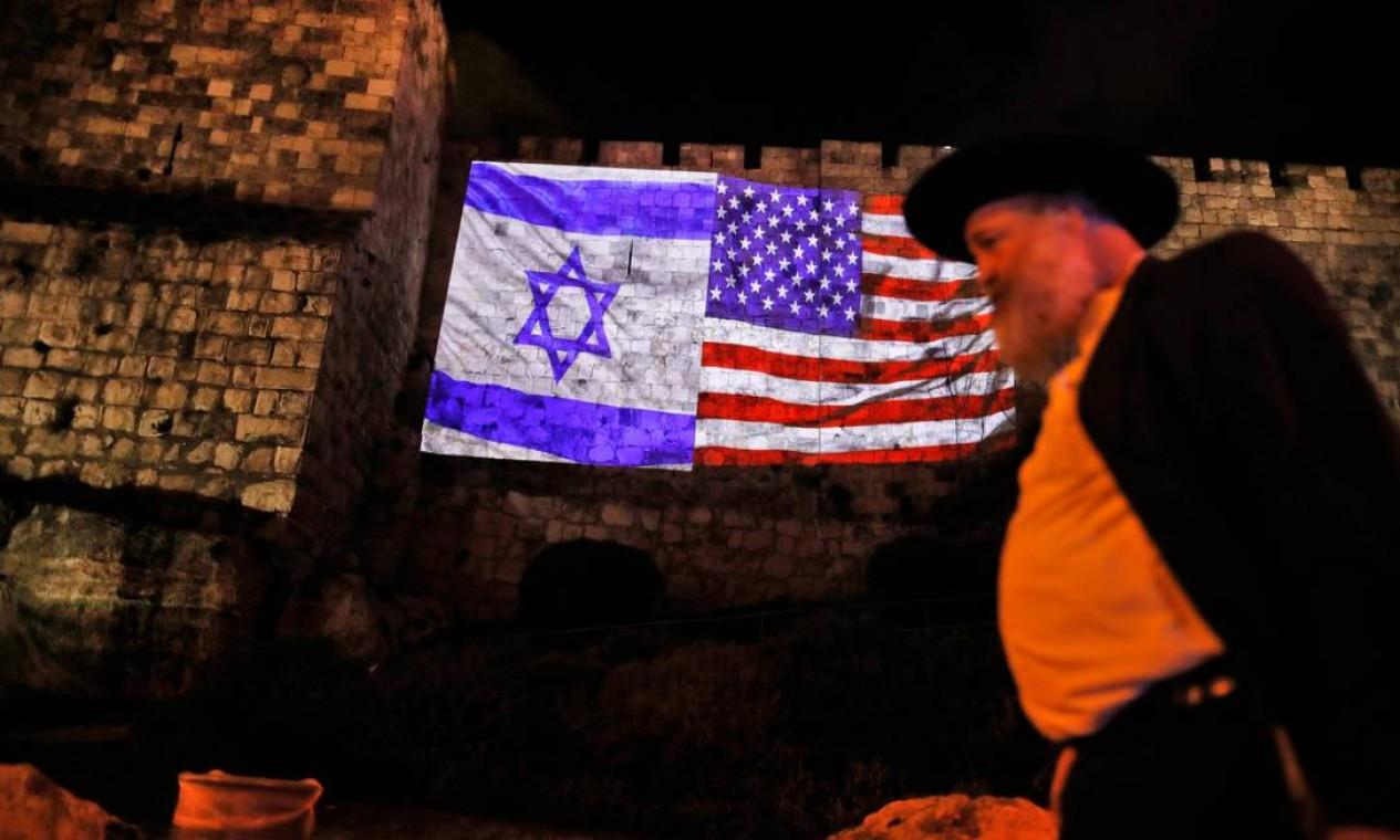 Homem passa em frente às bandeiras americana e israelense nos muros da Cidade Velha de Jerusalém. Decisão de Trump de reconhecer cidade como capital de Israel diverge do consenso internacional Foto: AHMAD GHARABLI / AFP