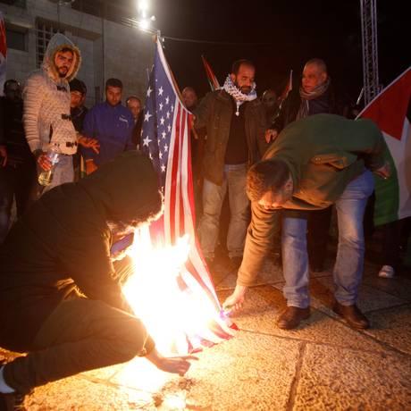 Manifestantes queimam bandeiras dos EUA em Belém, na Cisjordânia Foto: MUSA AL SHAER / AFP