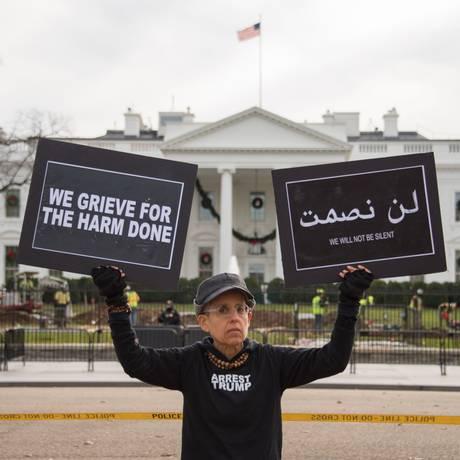 Manifestante exibe cartazes contra Trump com camisa 'Prendam Trump' Foto: MARI MATSURI / AFP