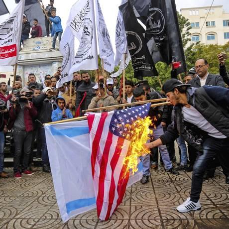 """Fúria nas ruas. Palestinos queimam bandeiras dos EUA e de Israel em Gaza: grupo radical Hamas disse que a decisão abriu """"as portas do inferno"""" para interesses americanos Foto: MAHMUD HAMS/AFP"""
