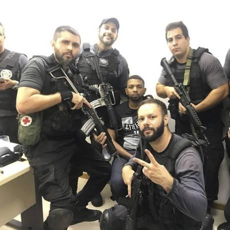 Para a posteridade. Policiais civis fazem foto com bandido que eles próprios capturaram Foto: Reprodução