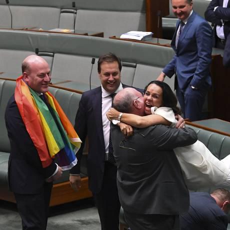 O deputado liberal Warren Entsch levanta a deputada trabalhista, Linda Burney, enquanto celebram a aprovação da lei que aprova o casamento gay na Câmara dos Representantes Foto: HANDOUT / REUTERS
