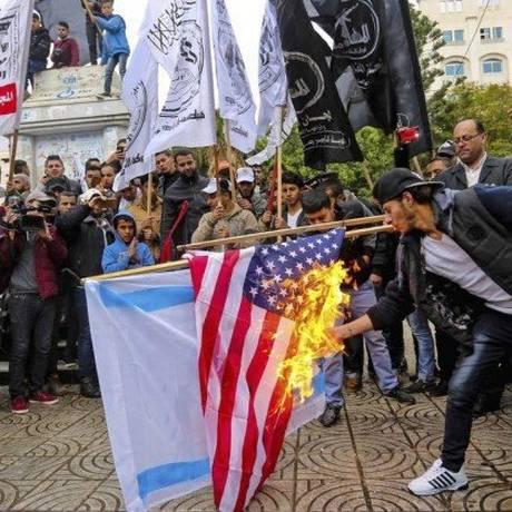 """Fúria nas ruas. Palestinos queimam bandeiras dos EUA e de Israel em Gaza: grupo radical Hamas disse que a decisão abriu """"as portas do inferno"""" para interesses americanos Foto: MAHMUD HAMS / AFP"""
