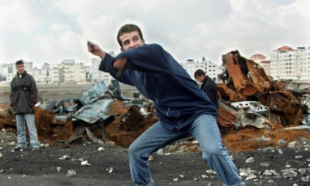 Palestino prepara estilingue para atacar tropas israelenses na Cisjordânia em janeiro de 2001, durante a Segunda Intifada Foto: Jamal Aruri / AFP