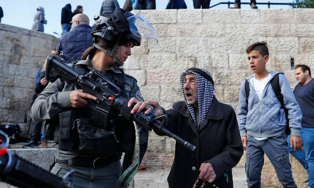 Um senhor palestino aborda soldado israelense que tenta dispersar protestantes na Cidade Velha de Jerusalém AHMAD GHARABLI / AFP