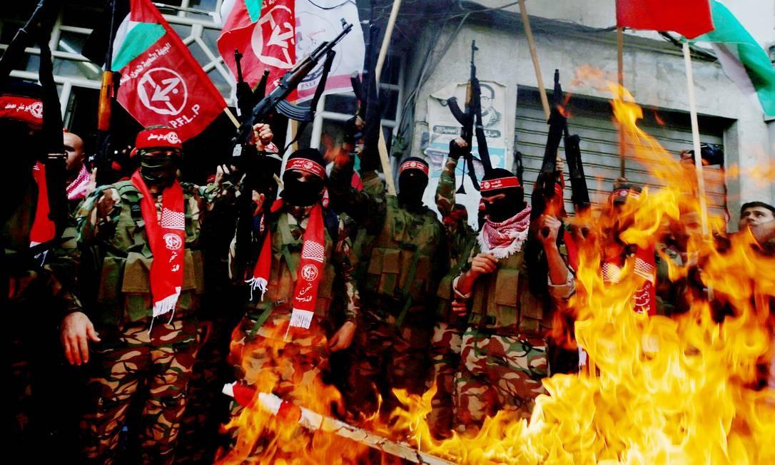 Militantes da Frente Popular de Libertação da Palestina (PFLP) queimam bandeiras dos EUA e de Israel na Faixa de Gaza MOHAMMED SALEM / REUTERS