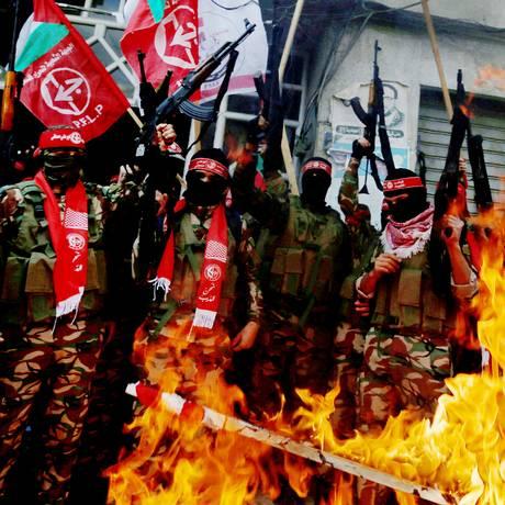 Militantes da Frente Popular de Libertação da Palestina (PFLP) queimam bandeiras dos EUA e de Israel na Faixa de Gaza Foto: MOHAMMED SALEM / REUTERS