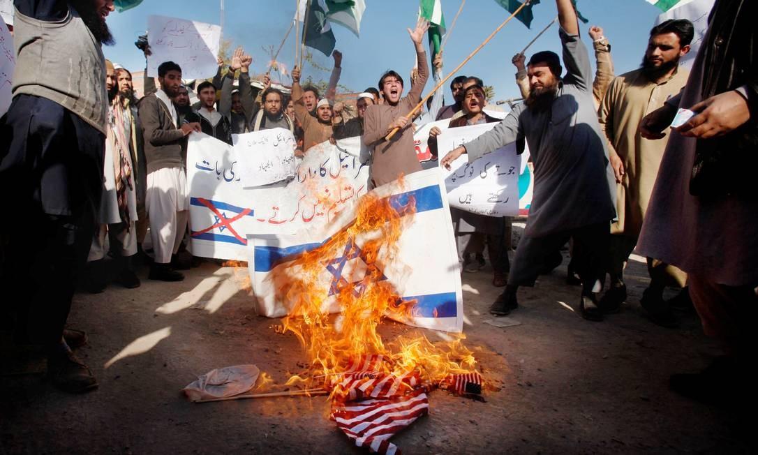 Apoiadores de uma organização islâmica queimam as bandeiras de Israel e Estados Unidos em protestos contra a decisão diplomática americana FAYAZ AZIZ / REUTERS