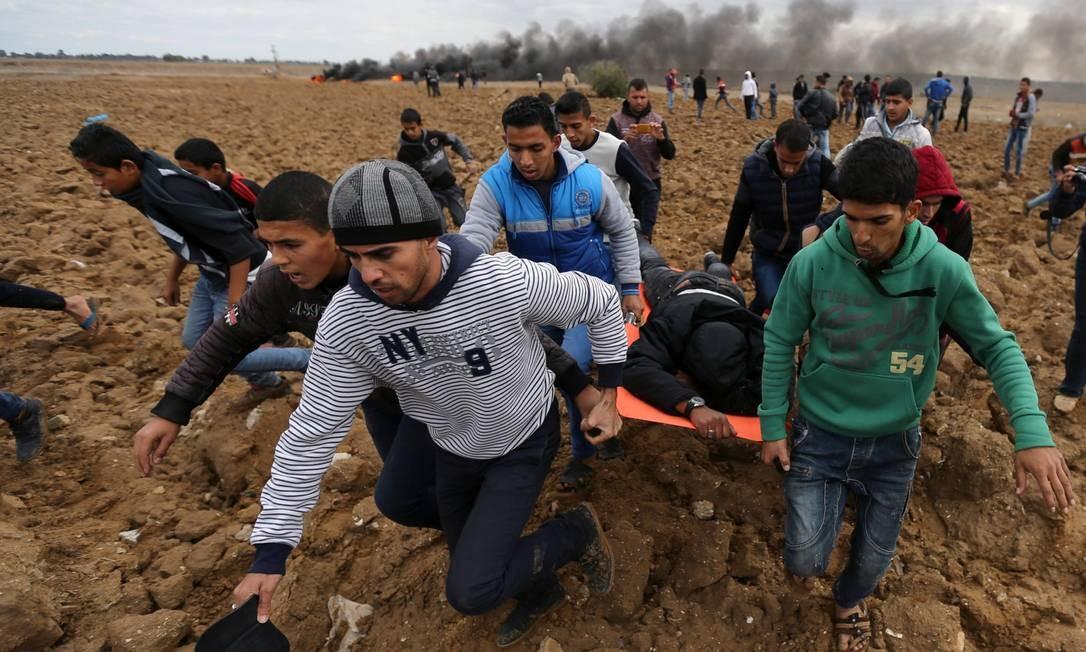 Palestinos carregam manifestante ferido após confronto com Exército iraelense IBRAHEEM ABU MUSTAFA / REUTERS