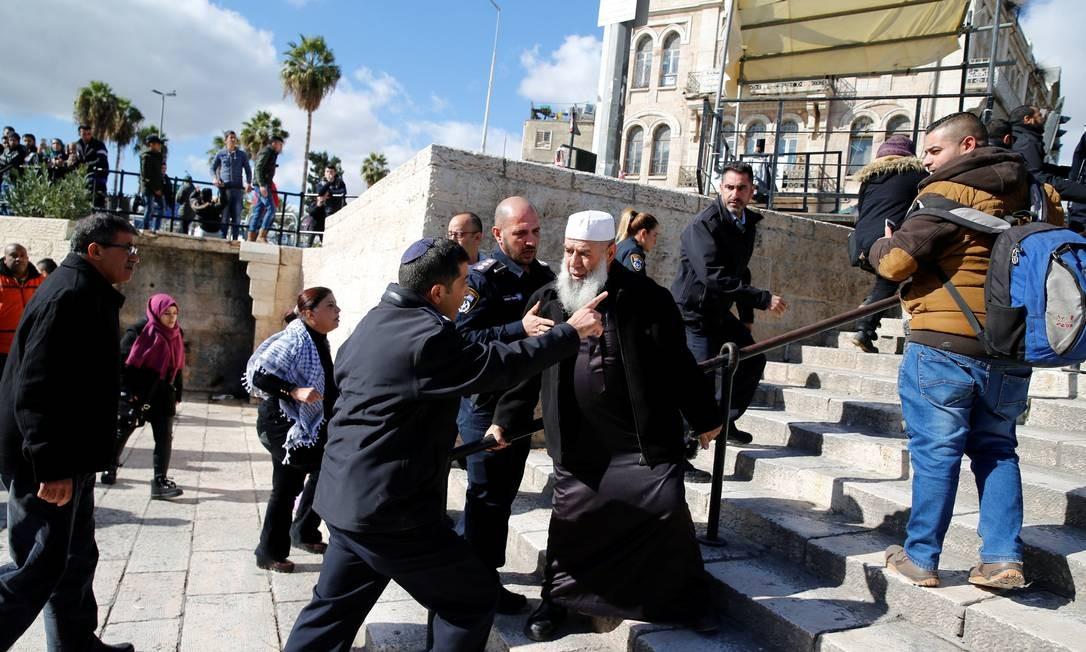 """Policial israelense distute com palestino durante protesto. O presidente da Autoridade Nacional Palestina, Mahmoud Abbas, imediatamente após a decisão entrou em contato com o presidente do Egito, Abdel Fattah al-Sisi. Abbas afirmou que os EUA """"perderam seu papel mediador na construção da paz"""" e encorajam os assentamentos e ocupação israelenses em territórios palestinos AMMAR AWAD / REUTERS"""