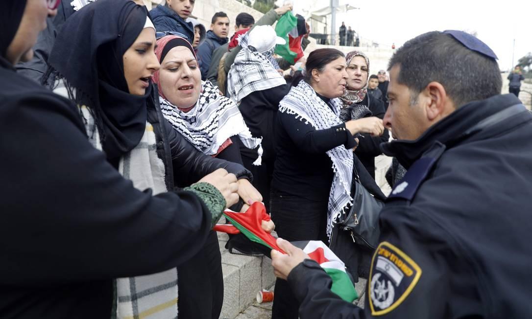 Soldado Israelense tenta tirar a força bandeira da Palestina das mãos de manifestantes MENAHEM KAHANA / AFP