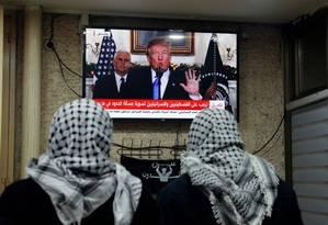 Homens palestinos assistem a discurso de Donald Trump, no qual presidente dos EUA reconheceu Jerusalém como capital de Israel Foto: AHMAD GHARABLI / AFP