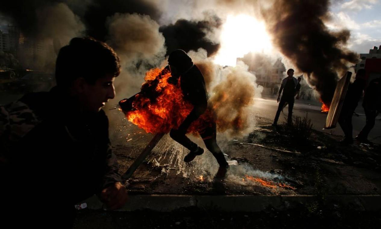 Manifestante palestino corre durante confrontos com tropas israelenses, em Ramallah Foto: ABBAS MOMANI / AFP