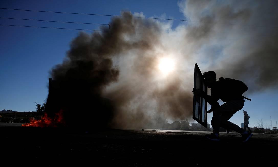 """Palestino tenta se proteger durante confronto com tropas israelenses. Os protestos no chamado """"Dia da Fúria"""" são uma resposta a decisão dos EUA de reconhecer Jerusalém como capital de Israel MOHAMAD TOROKMAN / REUTERS"""