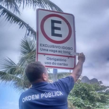 Um fiscal retira um adesivo que cobria parte da placa do Rio Rotativo Foto: Divulgação