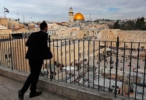 Homem observa o Muro das Lamentações, com o Domo da Rocha ao fundo: sincretismo religioso marca a Cidade Velha de Jerusalém Foto: THOMAS COEX / AFP