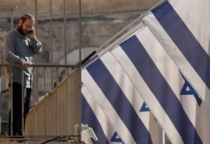 Homem judeu é clicado entre bandeiras israelenses na Cidade Velha de Jerusalém Foto: GORAN TOMASEVIC / REUTERS