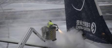 Degelo. Funcionário tenta descongelar asa de um avião chinês no Aeroporto de Frankfurt Foto: Andreas Arnold / AP