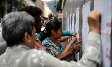 Venezuelanos observam listas eleitorais em Caracas Foto: FEDERICO PARRA / AFP