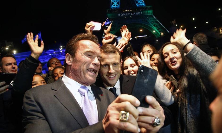 O presidente da França, Emmanuel Macron e Arnold Schwarzenegger fazem selfie com jovens na frente da Torre Eiffel, em Paris Foto: Thibault Camus / AP