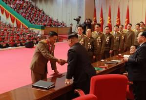 O líder da Coreia do Norte, Kim Jong-un, condecora cientistas que ajudaram no desenvolvimento de míssil balístico internacional Foto: KCNA / AFP